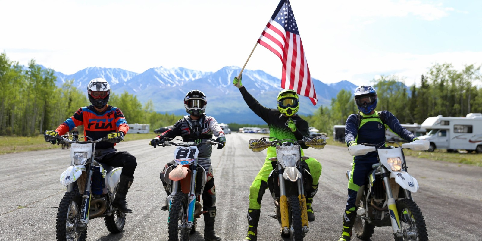 Warrior Built member Chris Colmenero sits on his dirt bike next to two other active duty service members and a veteran.