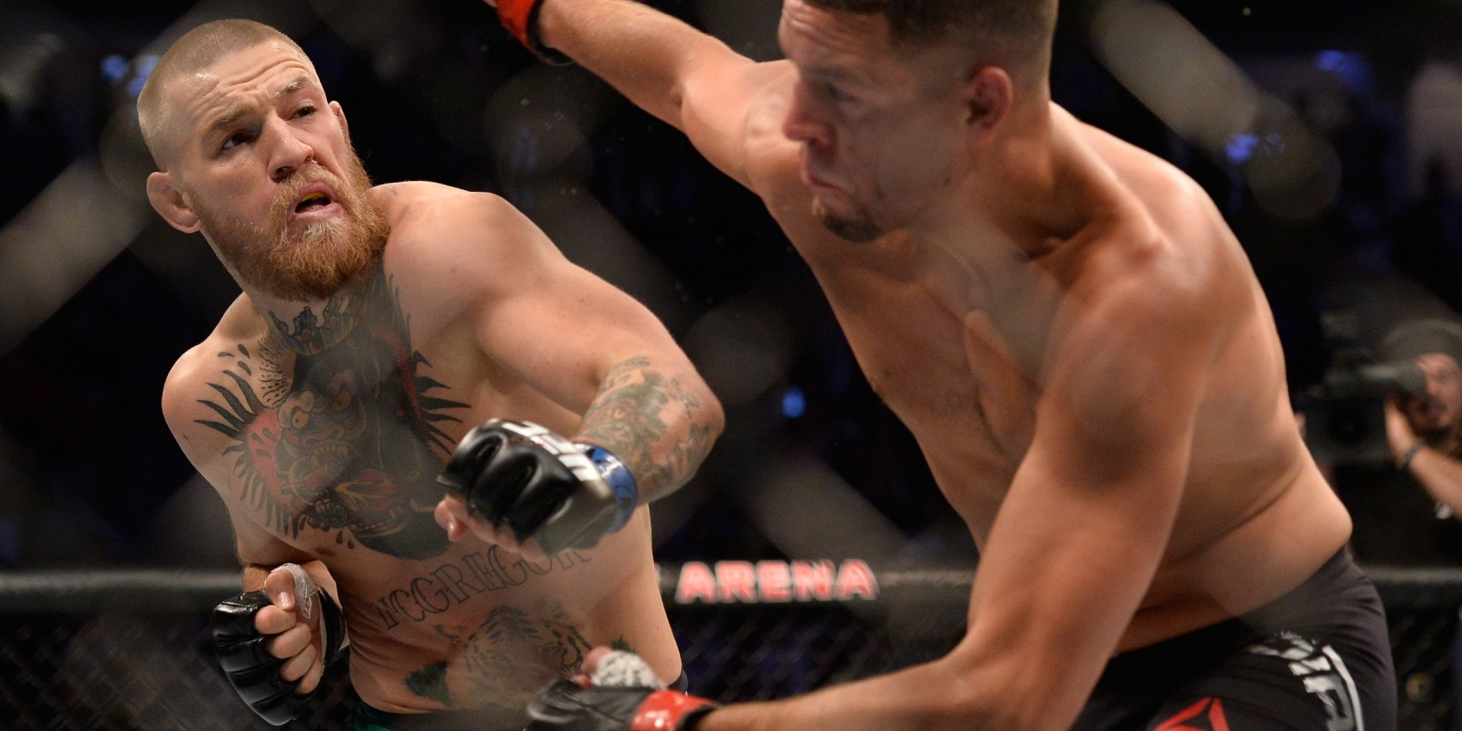 Conor McGregor punches Nate Diaz in their welterweight bout during the UFC 202 event at T-Mobile Arena on August 20, 2016 in Las Vegas, Nevada.
