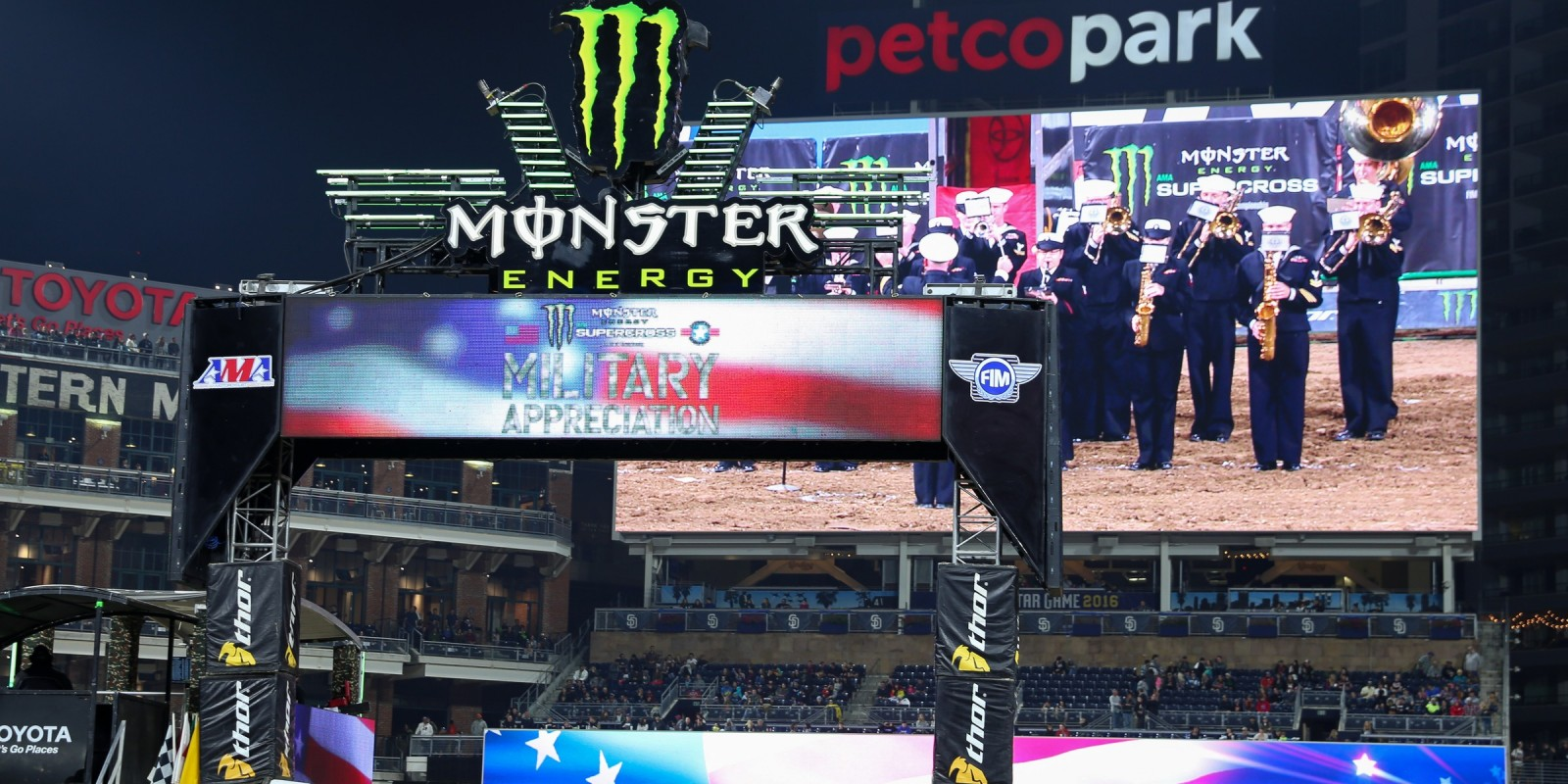 The U.S. Navy Band plays on the big screen as troops line the field.