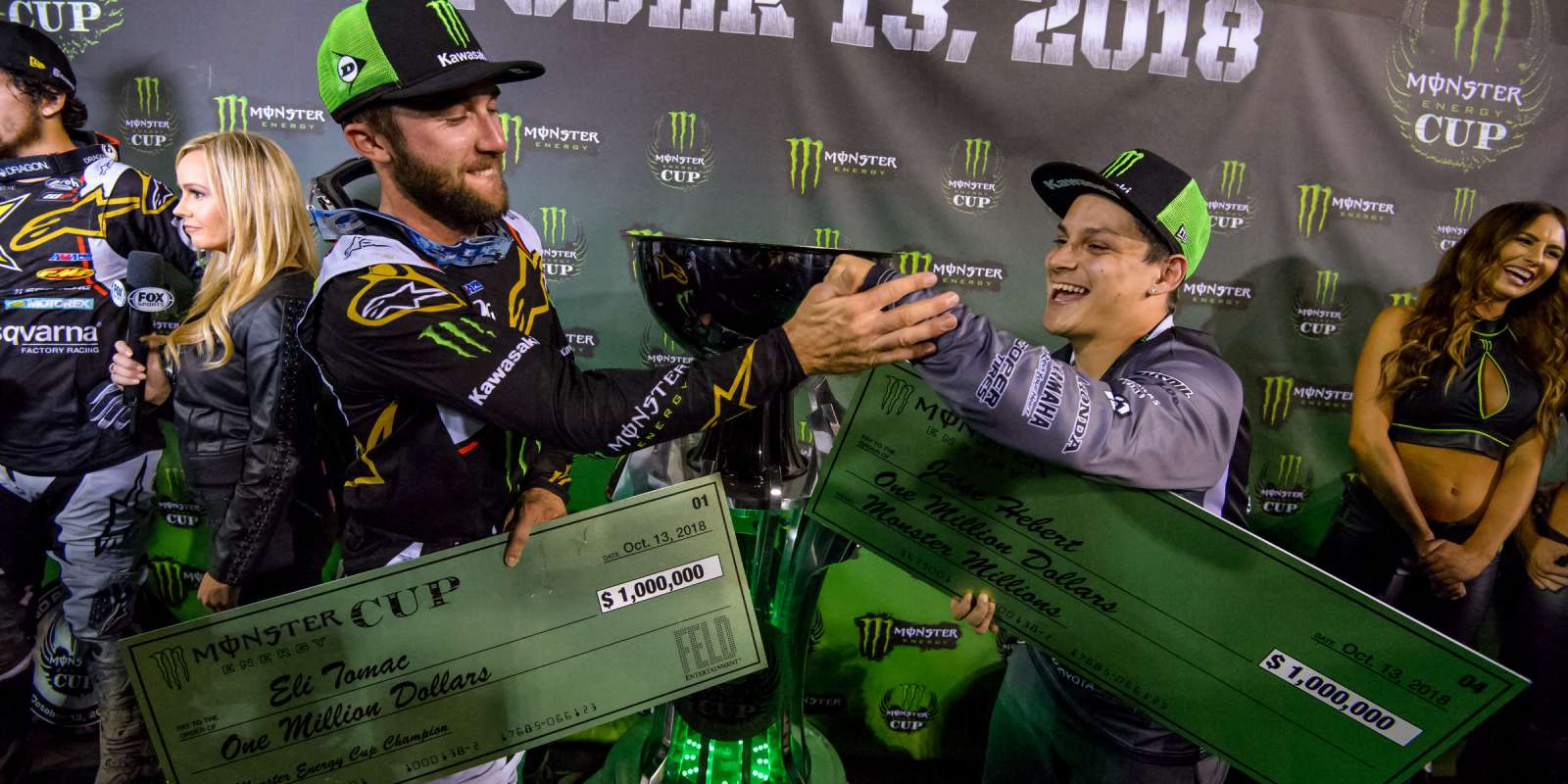 Eli Tomac and contestant winner Jesse Hebert on the podium holding their Monster Millions check