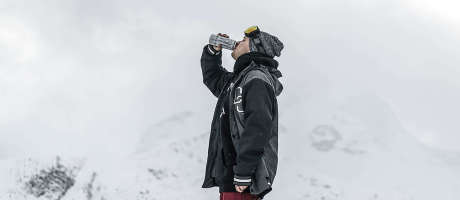 A snowboarder drinking Monster Ultra